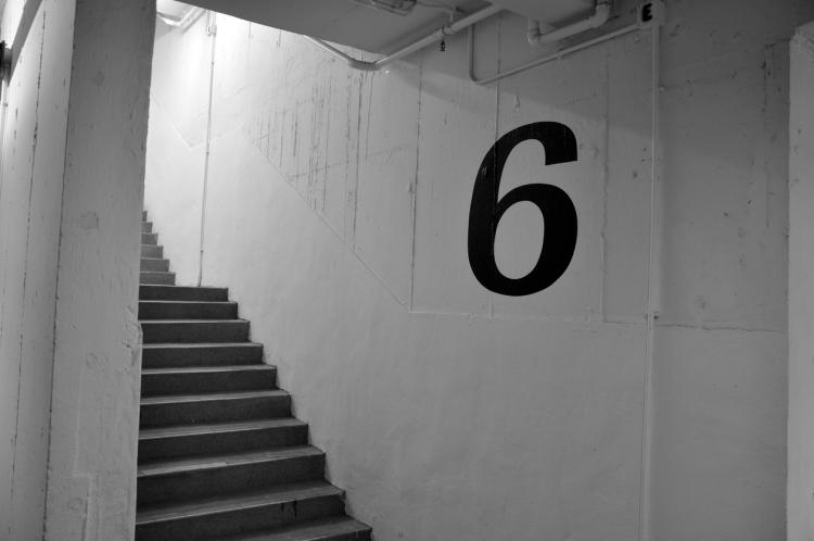 The number 6 painted on the wall of a stairwell