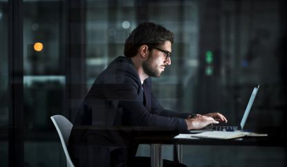 Agile team member working on a laptop in a dark office