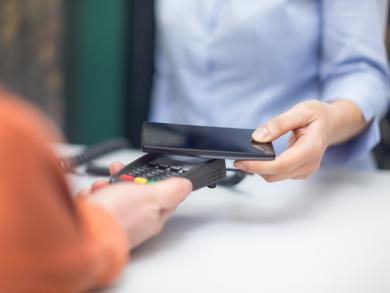 Person using smartphone to pay on eftpos machine